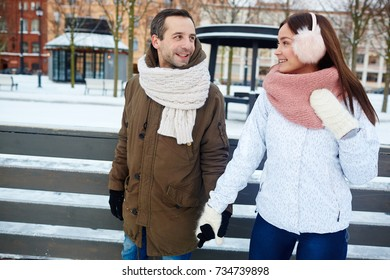 Cheerful couple having fun on skating-rink on winter day