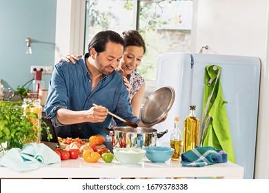 Fröhliches Paar in der Küche, das eine italienische Sauce zubereitet