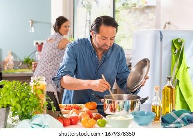 Cheerful Couple in the kitchen preparing an Italian sauce