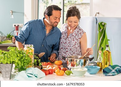 Cheerful Couple in the kitchen preparing an Italian sauce