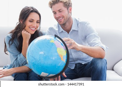 Cheerful couple looking at a globe in the living room