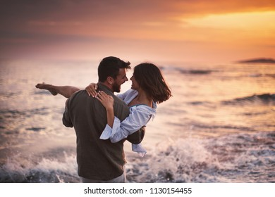 Cheerful couple in love at seaside on beautiful sunset. Side view. Horizontal.