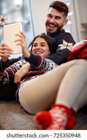 Cheerful couple making Christmas sefie together in bed