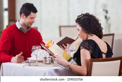 Cheerful couple with menu in a beautiful restaurant making order