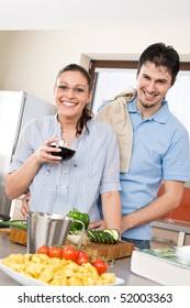 Cheerful couple in modern kitchen cook together, drink red wine