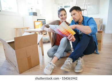 Cheerful couple moving in new home, choosing wall paint colours