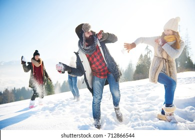 Cheerful couple playing in the snow