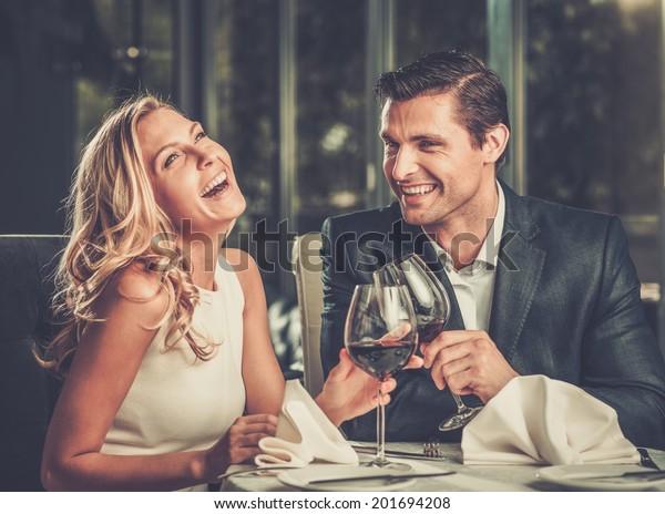 Веселая пара в ресторане с бокалами красного вина