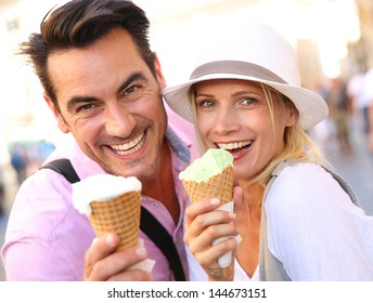 Cheerful couple in Rome eating ice cream cones
