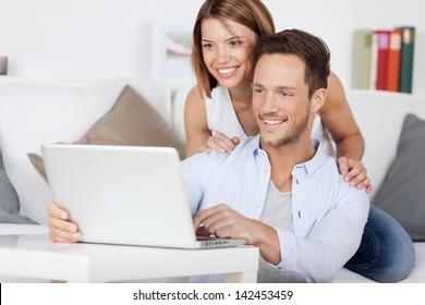 Cheerful couple searching something on laptop at home