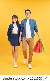 cheerful couple with shopping bags isolated on yellow