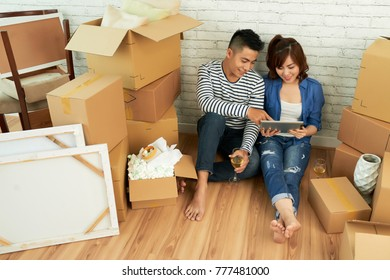 Cheerful couple sitting among cardboard boxes in their new apartment