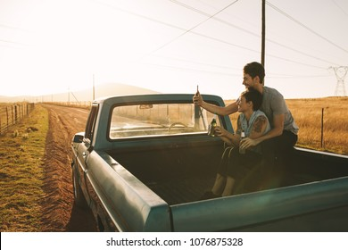 Cheerful couple sitting in the back of their pickup truck enjoying the road trip in country side. Couple taking a selfie using mobile phone sitting at the back of their pick up truck.
