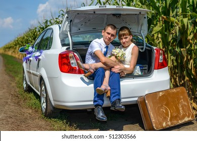 Cheerful couple sitting in car trunk with bouquet and suitcase outside beside corn stalks