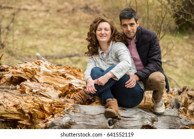 Cheerful couple sitting on a trunk  tree  and posing together