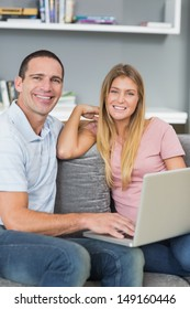 Cheerful couple sitting using laptop on the couch together in sitting room at home