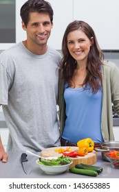 Cheerful couple smiling at camera and preparing vegetables in their kitchen