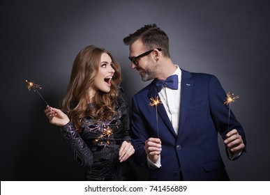 Cheerful couple with sparkler flirting
