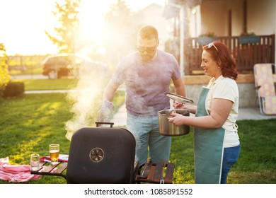 Cheerful couple is taking steamy meat off the grill and putting it in a pot on a beautiful day.