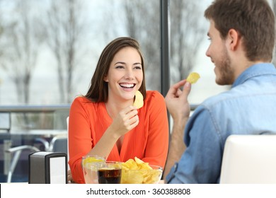 Cheerful couple talking and eating chip potatoes looking each other dating inside a coffee shop with an exterior background