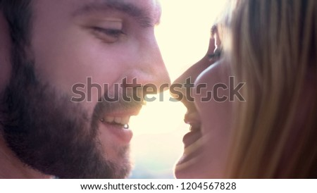 Cheerful couple tenderly looking at each other, preparing for kiss, dating