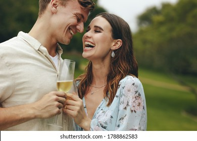 Cheerful couple together outdoors holding a glass of wine. Caucasian man and woman with a drinks standing together at park.