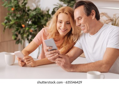 Cheerful couple using digital gadgets at home