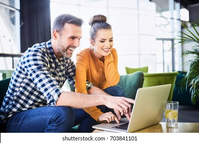 Cheerful couple using laptop browsing and pointing fingers at screen while in modern restaurant
