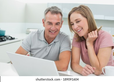 Cheerful couple using laptop in the kitchen at home
