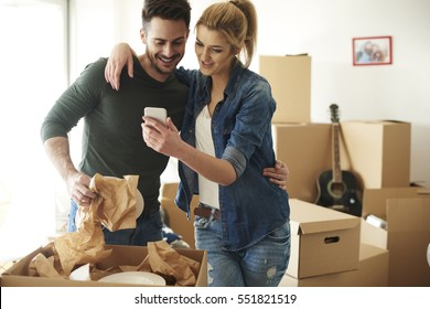 Cheerful couple using phone while moving house