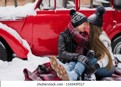 Cheerful couple in warm cozy clothes near red vintage car covered with snow in the garden. Cold happy winter day. Holidays, Christmas, New Year, winter, love, beauty concept.