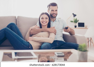 Cheerful couple is watching tv together and having fun. They are in the living room of their apartment