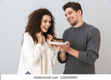 Cheerful couple wearing sweaters standing isolated over gray background, celebrating birthday, holding piece of cake with candle