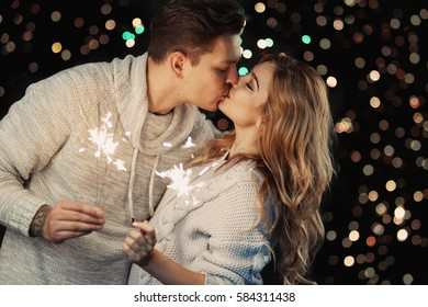 Cheerful couple in winter clothes hugging and kissing. Low light