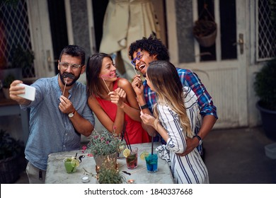 Cheerful couples taking funny selfie at the open air birthday party on a beautiful summer dusk. Quality friendship time together