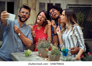 Cheerful couples using funny accessories for selfie at the open air birthday party on a beautiful summer dusk. Quality friendship time together