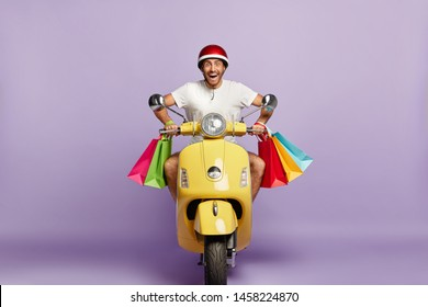 Cheerful courier has home delivery, drives motorbike with colorful shopping bags, wears helmet, greet customers in friendly manner. Cheerful man returns from shopping in good mood, has own transport