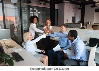 Cheerful coworkers different ages and ethnicity gathered together in coworking shared office room giving high five celebrating congratulating each other with good deal and success at common business