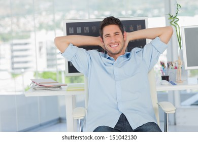 Cheerful creative business employee resting on his swivel chair
