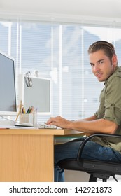 Cheerful creative business employee working on computer in a modern office