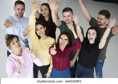 Cheerful crew of young startuppers raising hands celebrating finnishing sucessful project feeling happy together in coworking office, positive male and female students enjoying friendly atmosphere