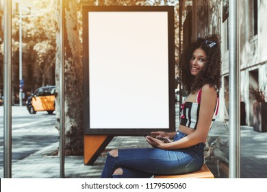 A cheerful curly cute girl is sitting on the metal bench of an urban bus stop, holding smartphone while waiting for her transport, with blank white banner placeholder mock-up behind for your advert
