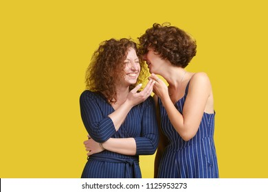 Cheerful curly hairstyle girls gossip. Charming caucasian woman tells funny story to her best friend in ear, joke causes a smile and laughter. Communication concept, friendship, yellow background