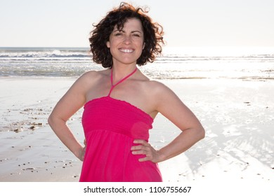 cheerful curly woman brunette in pink dress sexy on sunset beach vacation day