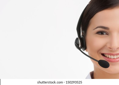 Cheerful customer service representative. Portrait of beautiful young female customer service representative in headset looking at camera and smiling while isolated on white