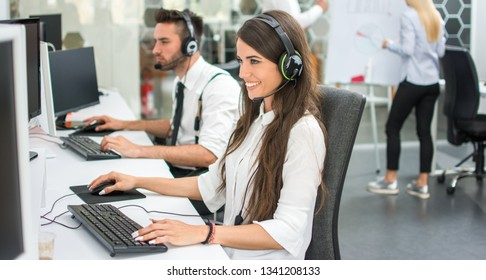 Cheerful customer support operators working in call center. Side view of smiling young business woman and business man talking with clients and solving problems on computers.