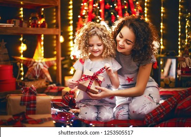 Cheerful cute curly little girl and her older sister exchanging gifts. Sisters having fun near christmas tree indoors. Loving family with presents in christmas room.