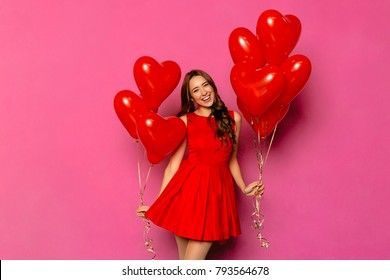 Cheerful cute girl with long curly hair in red dress holding air balloons, posing at camera. St. Valentine's day.