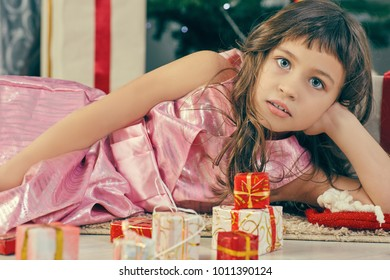 Cheerful cute little child girl with present. Little girl lies among the Christmas gifts.