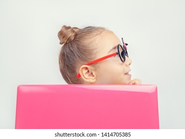 Cheerful cute little girl using laptop computer and looking at side. Portrait of caucasian little girl behind laptop computer. Pretty girl Girl enjoying modern generation technologies